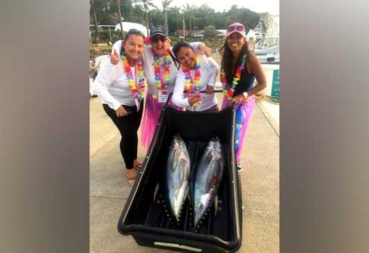 Un grupo de cuatro mujeres posa con un par de peces vela