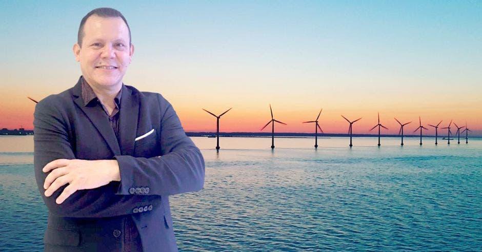 Un señor de mediana edad posa en el mar con turbinas eólicas de fondo