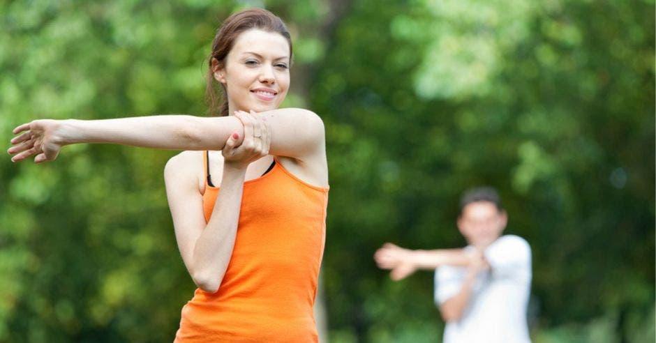 persona haciendo ejercicio al aire libre con camisa anaranjada