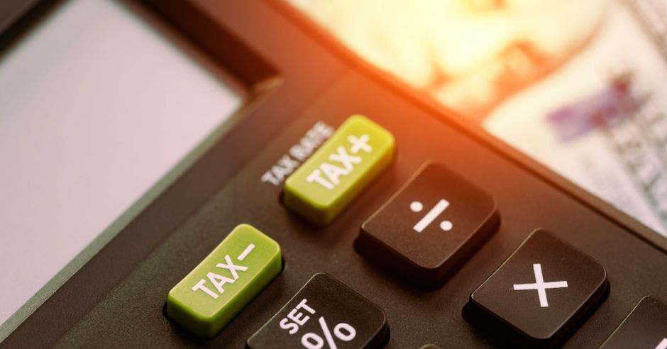 Calculadora con la palabra tax con signos de más y menos en verde