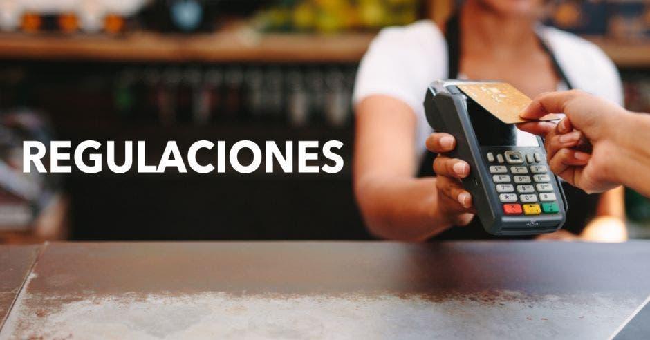 Una persona paga en un comercio con una tarjeta de manera contactless en un datáfono