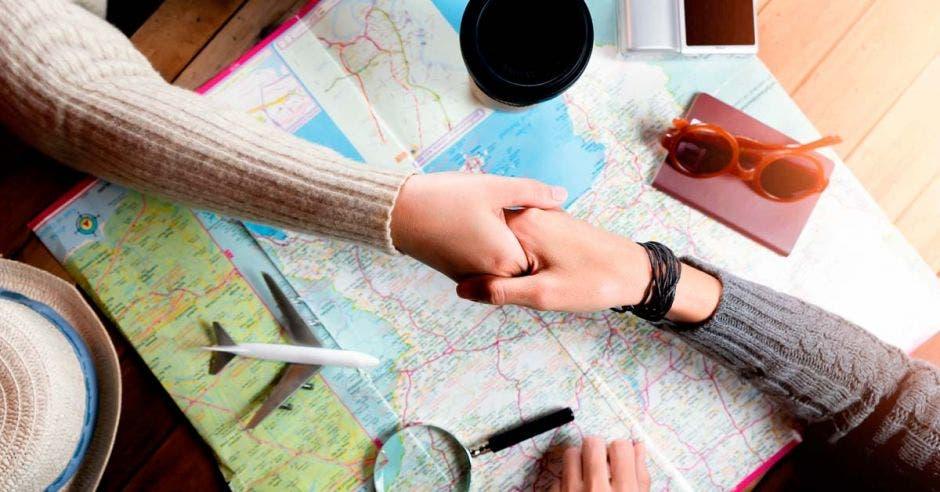 Personas se dan un apretón de manos sobre un mapa, lupa y avión a escala haciendo un trato de un viaje