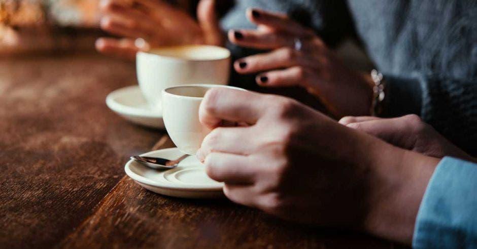 Dos comensales disfrutan de una taza de café