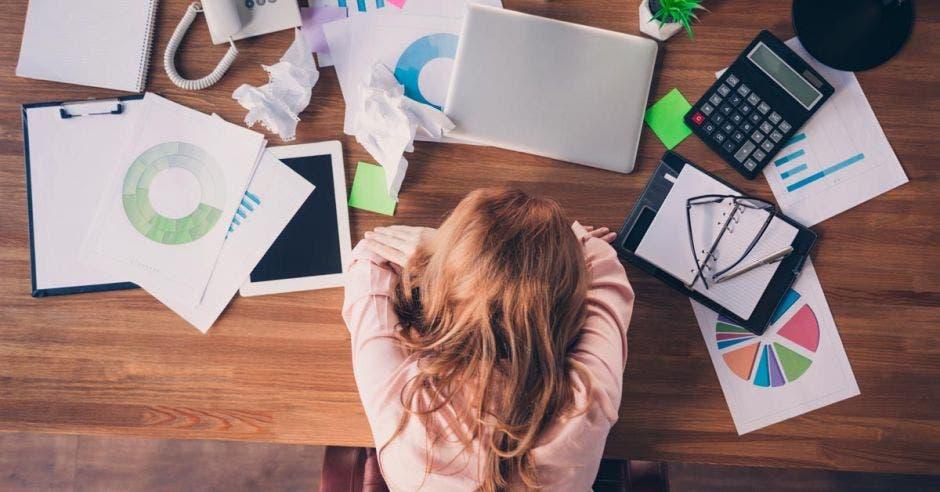 persona acostada en una mesa rodeada con gráficos, computadora, calculadora en modo de abrumada