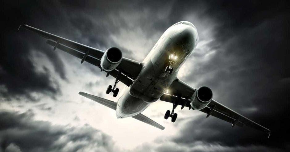 Un avión vuela sobre un cielo nublado