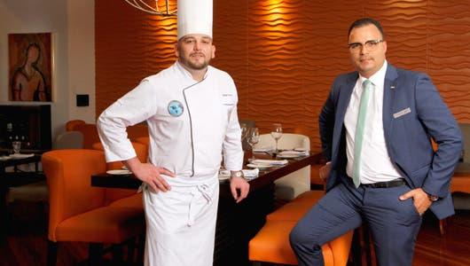 El chef con la vestimenta de trabajo, junto al gerente de traje entero