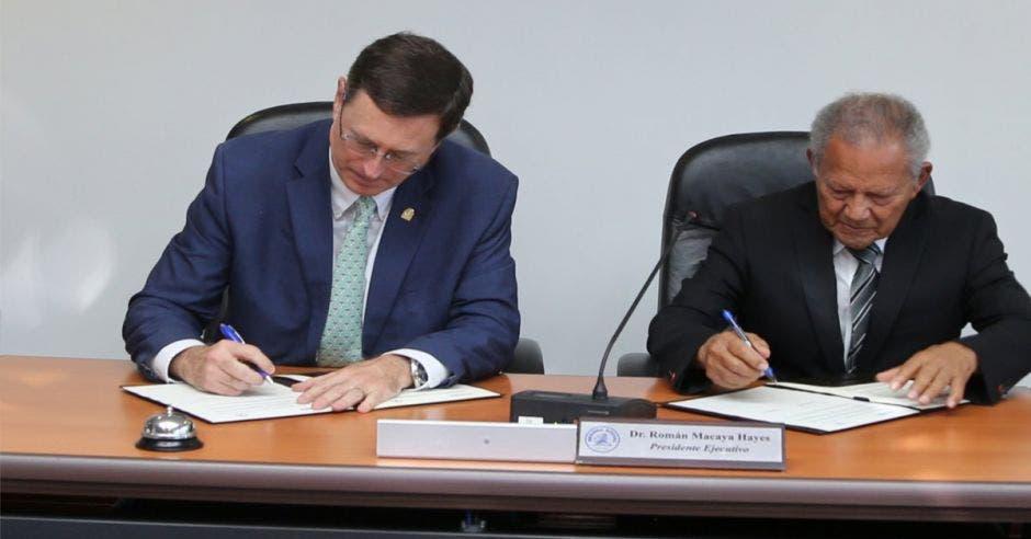 Román Macaya, el presidente de la Caja firmando el convenio con Israel Hernández, rector de Unibe