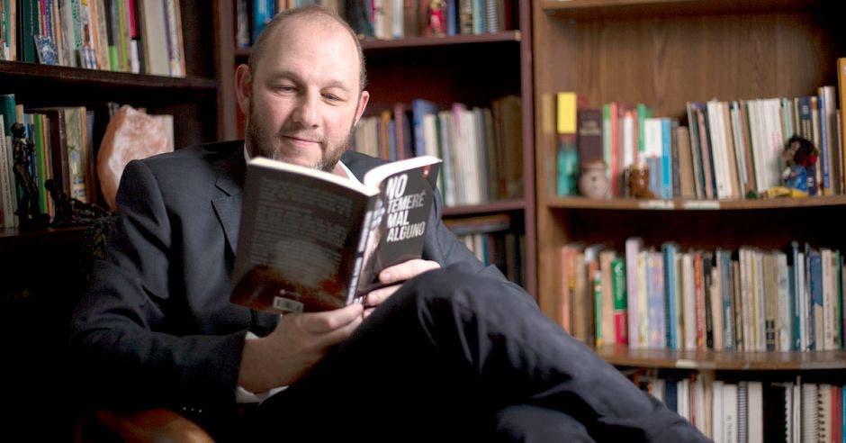 El escritor, un caballero blanco de barba, pelón, sentado en una biblioteca leyendo, mientras viste traje entero