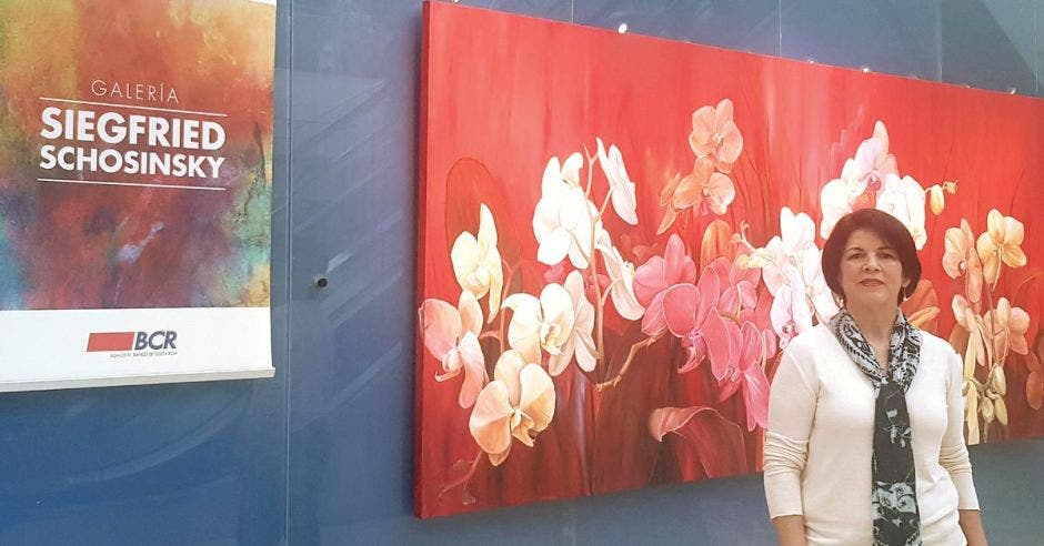 la artista nacional María Nielsen Alvarado de blusa blanca y bufanda verde, al lado de una de sus obras de orquídeas