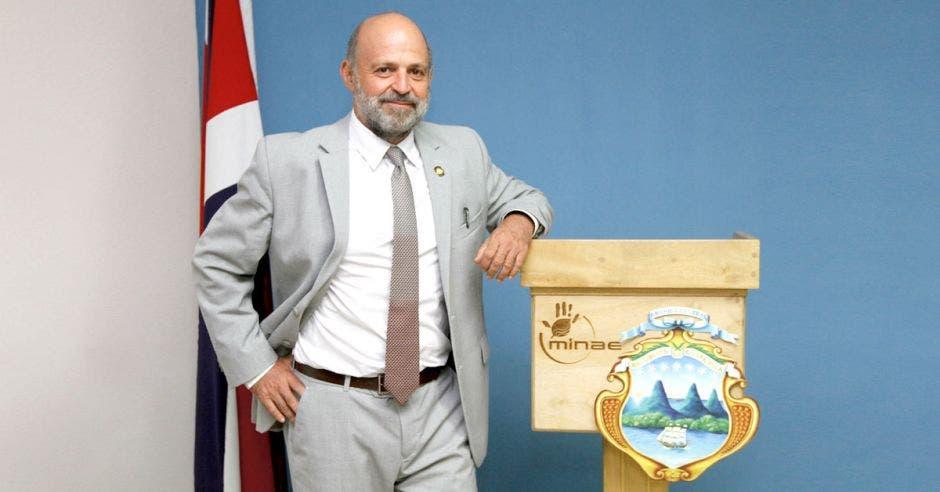 Ministro Carlos Manuel Rodr[iguez posa junto a un atril que tiene el escudo de Costa Rica