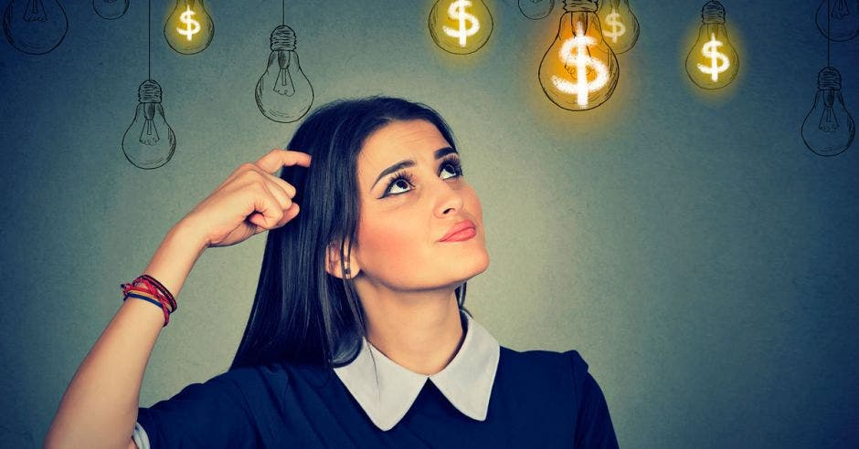 mujer pensativa con bombillos con signos de dólar encima