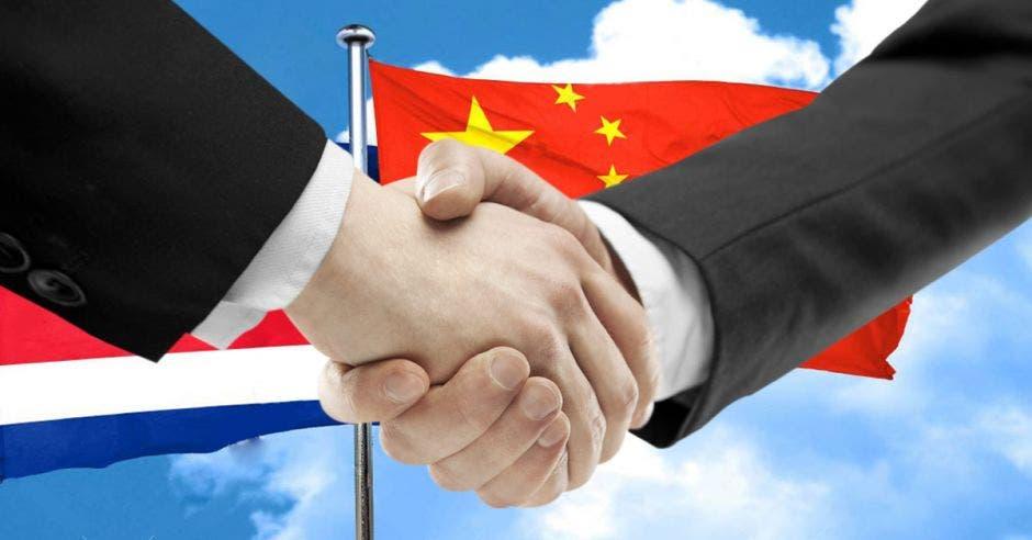 dos personas dándose la mano con banderas de Costa Rica y China de fondo