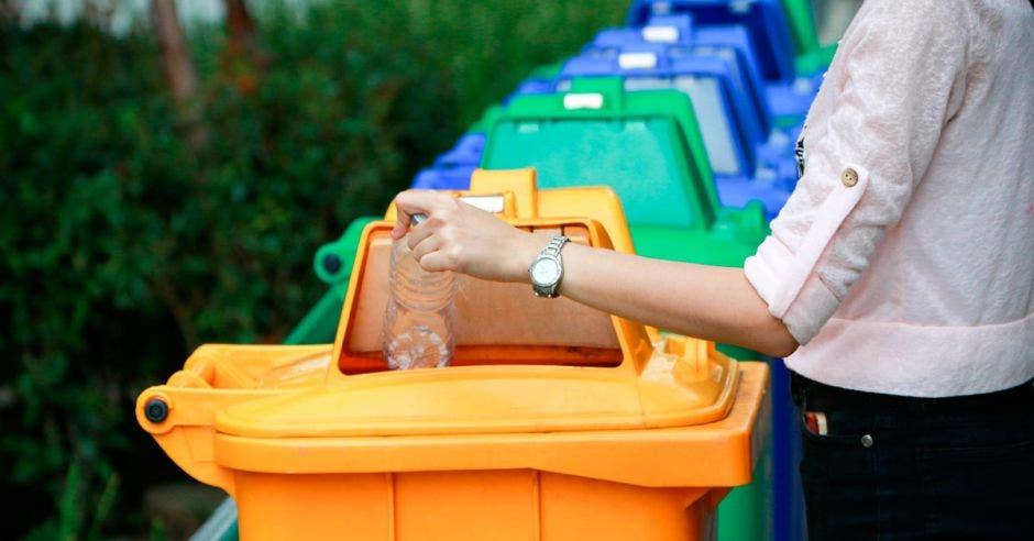 basureros de diversos colores y una persona depositando algo