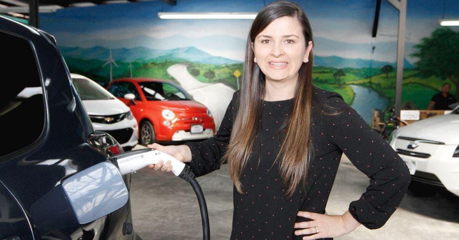 mujer enchufando carro electrico
