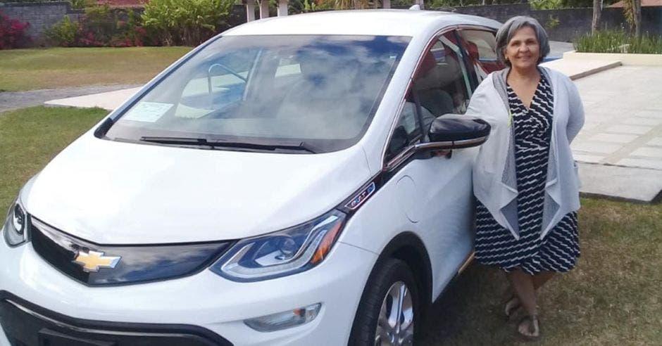 Una mujer de avanzada edad posa junto a un carro marca chevrolet color blanco