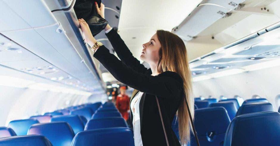 Estudiante colocando su equipaje de mano en un armario en el avión