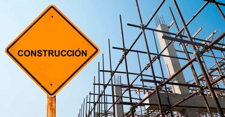 letrero con la palabra construcción, con un edificio en desarrollo detrás