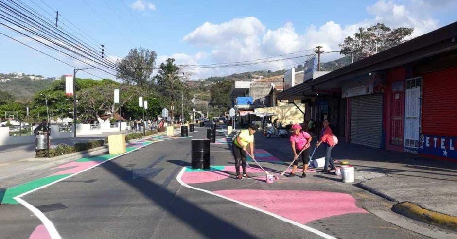 un  grupo de personas pinta una calle de color rosado