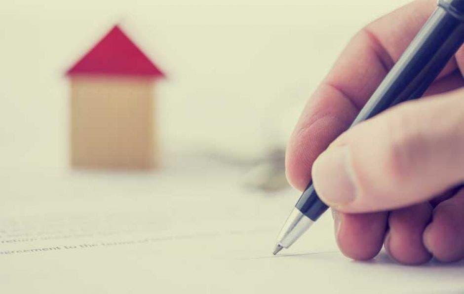 persona escribiendo con una casa de fondo