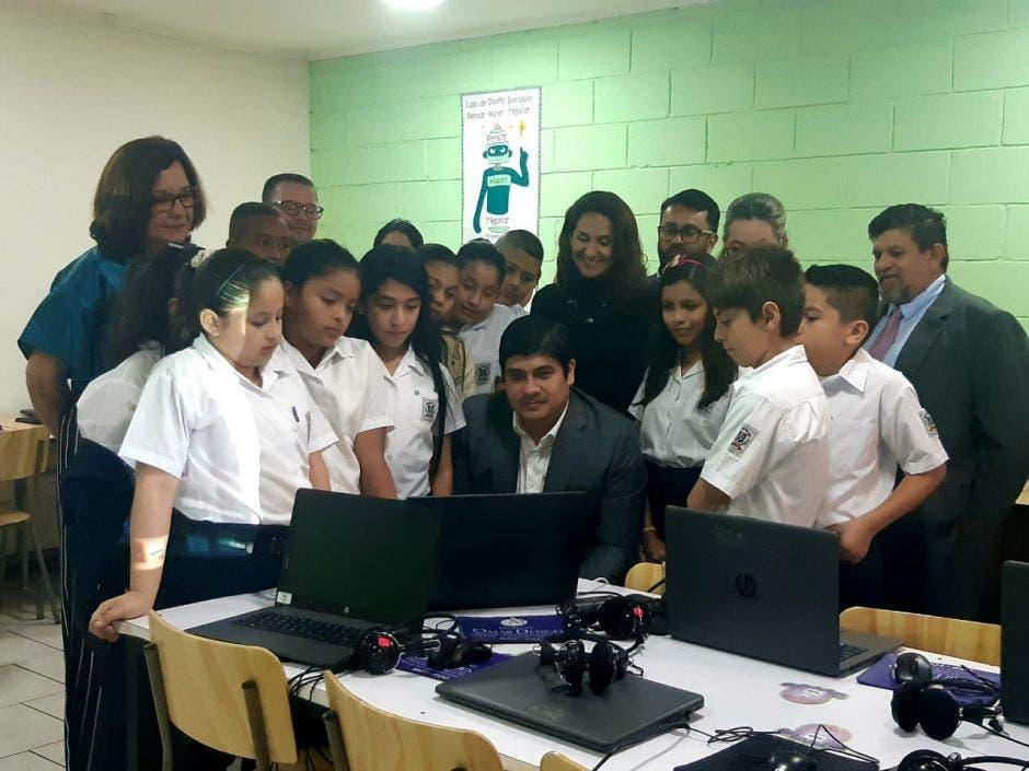 Unos niños viendo al Presidente usar una computadora