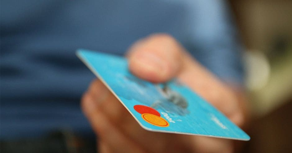 Persona mostrando una tarjeta de débito