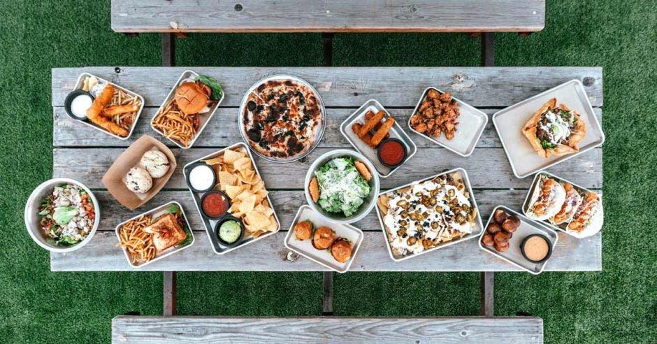 Una mesa llena de platillos de comida variados, entre ellos hamburguesas, papas fritas, emparedados y demás comidas artesanales
