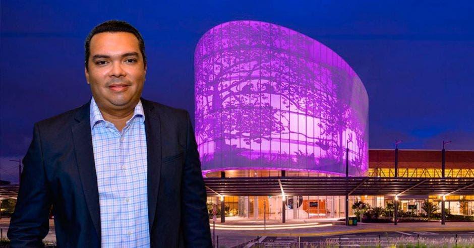 Un hombre de tez morena posa frente al centro de convenciones de noche