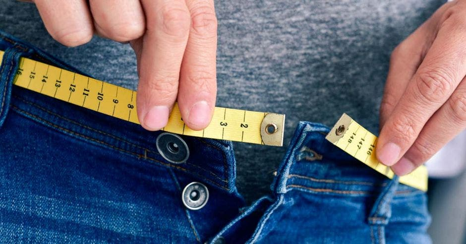 mujer midiendo su cintura con un metro