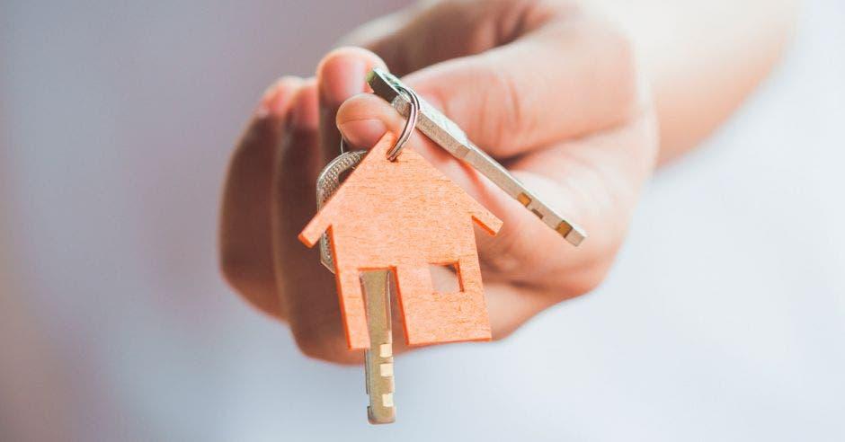 persona con unas llaves en la mano con un llavero en forma de casa