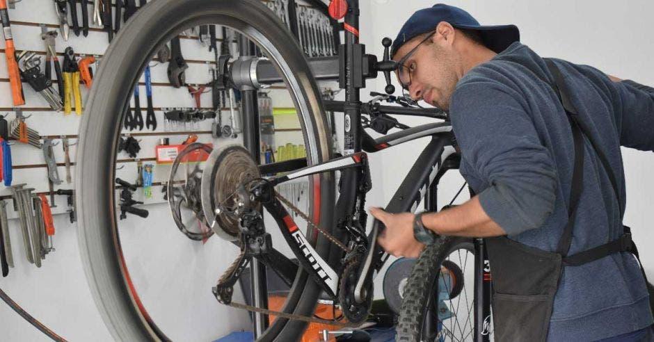 un hombre joven repara la llanta de una bicicleta