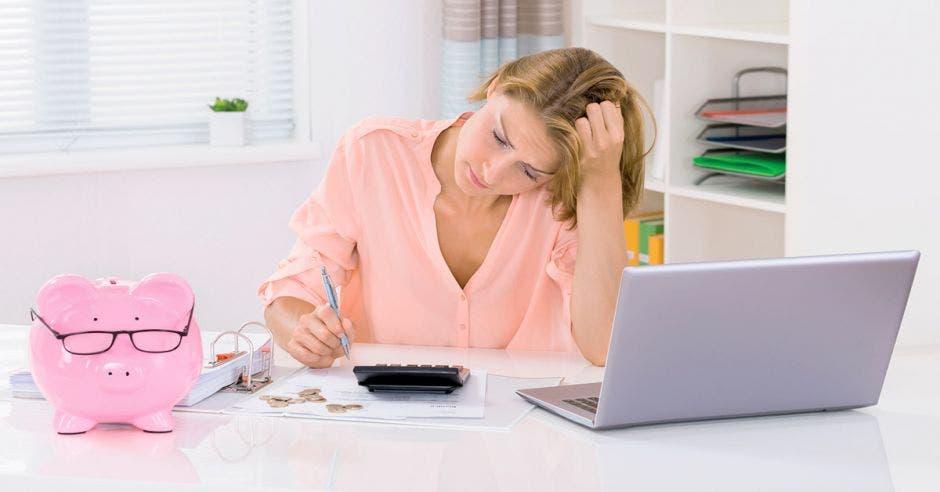 mujer pensativa haciendo un presupuesto frente a la computadora y una calculadora, y una alcancía de cerdito rosada al lado