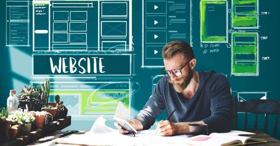 Un joven con lentes realiza unos apuntes en unas libretas, con un fondo de diseño web