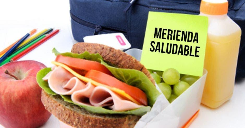 merienda de un sandwich y unas frutas con el letrero de merienda saludable