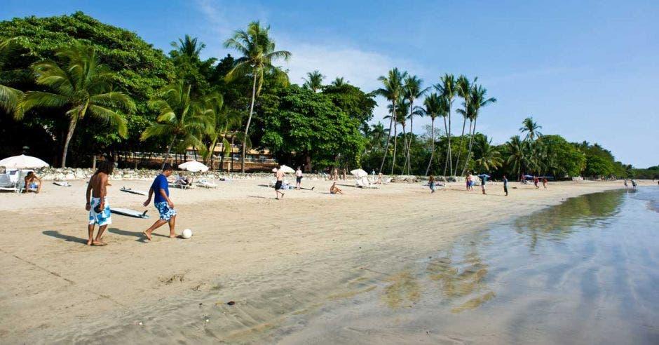 Varias personas juegan fútbol en la playa