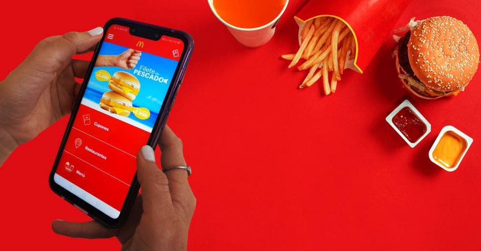 Una persona sostiene un celular con la app de Mcdonalds desplegada