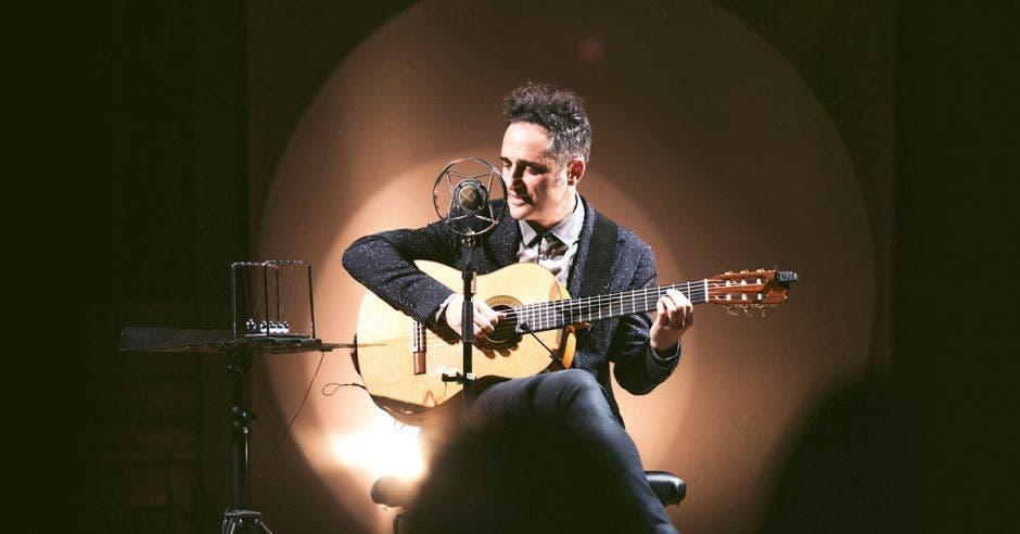Un músico toca su guitarra frente a un micrófono