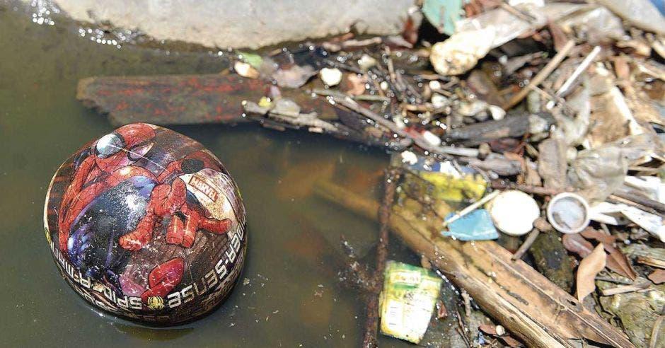 Una balón de plástico flota sobre un río color cafe