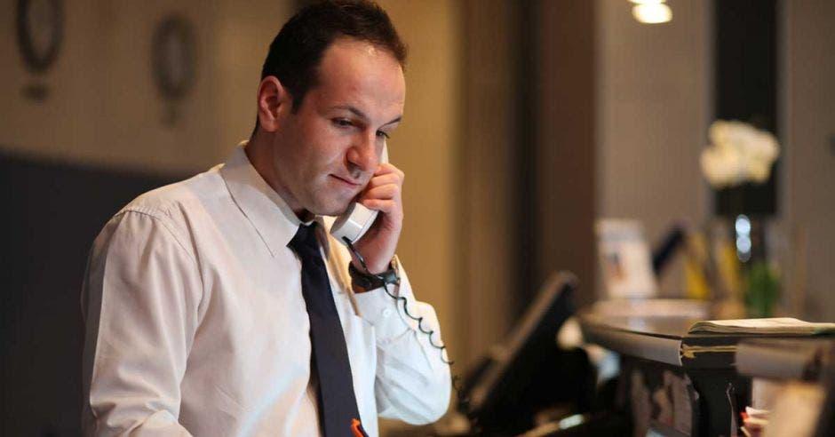 Un concierge atiende el telefóno en la recepción de un hotel