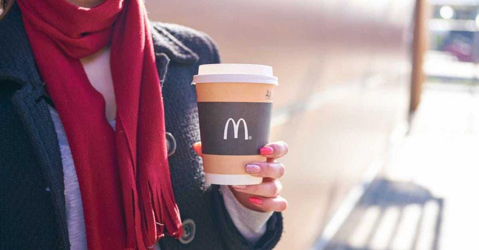 Una mujer con bufanda roja sostiene un café