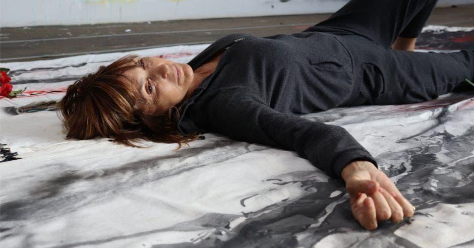 Artista Aimée acostada en el piso sobre lienzo