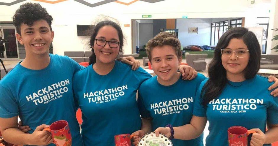 cuatro jovenes con camisas azules sostienen adornos alusivos a una actividad