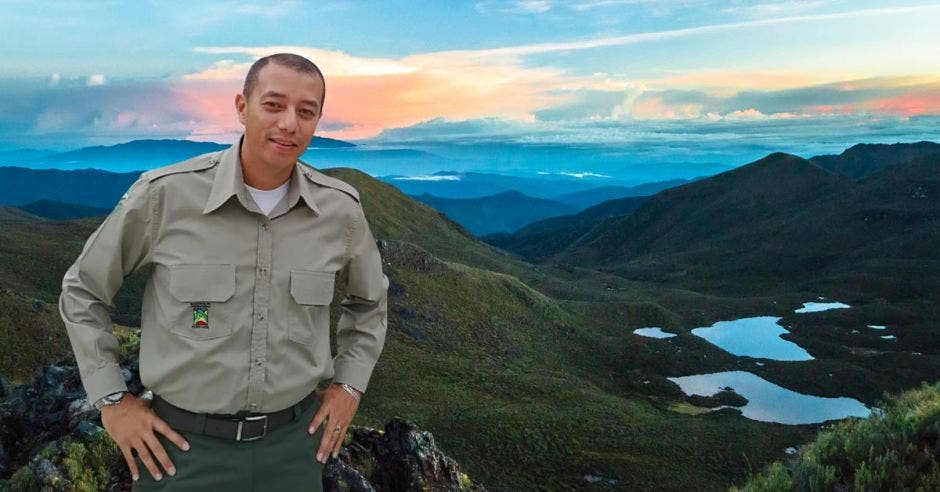 Un guardaparques posa junto a una montaña