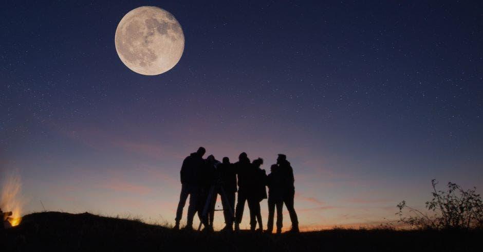 grupo de personas apreciando la luna