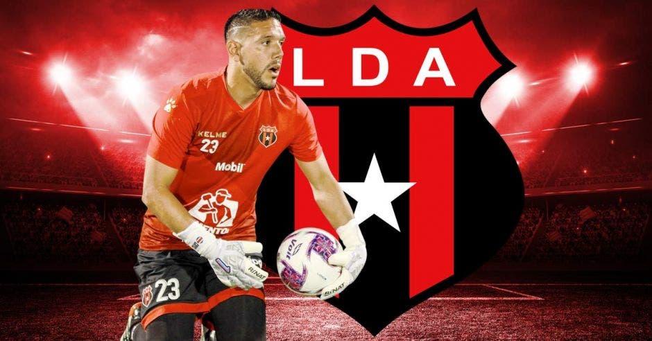 Moreira recoge un balón vestido con el uniforme de Alajuelense y con el escudo de la Liga de fondo