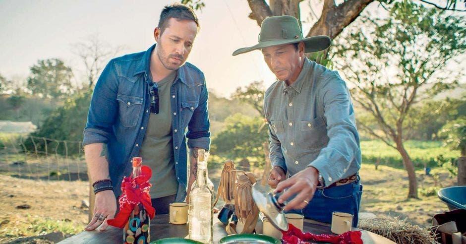 Dos chefs ven unos envases mientras están en medio de arboles