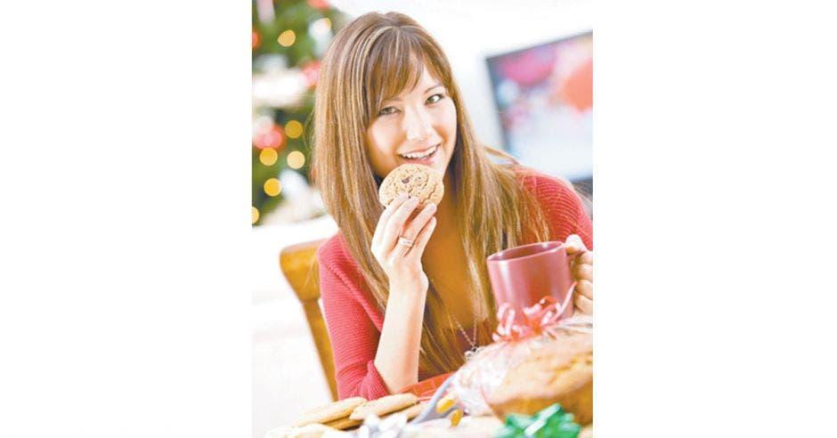 Mujer sosteniendo un vaso y en la otra mano una galleta