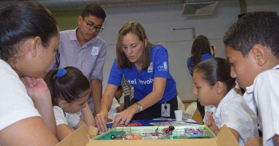 Una mujer con blusa azul imparte un taller de robótica