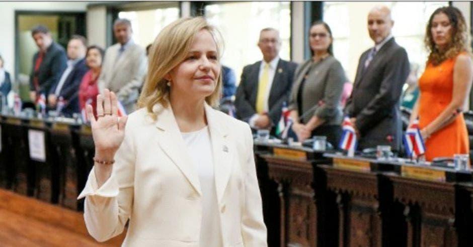 Catalina Crespo con un traje blanco levantando su mano izquierda en señal de juramento