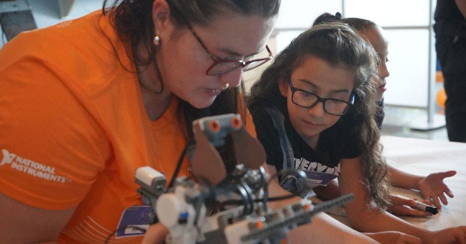 Una mujer voluntaria enseñándole a una niña sobre robótica