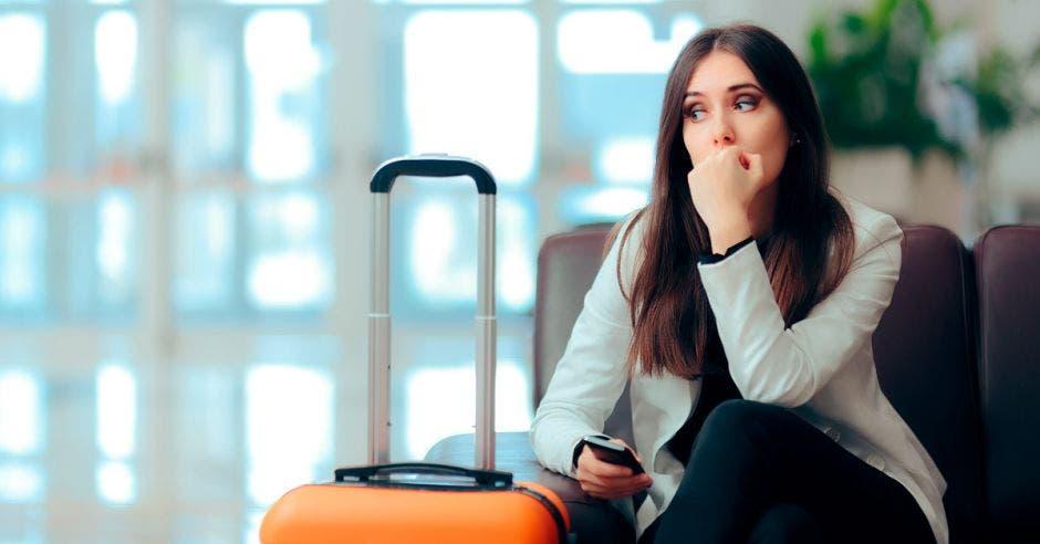 Una mujer espera con un maletín en un lobby